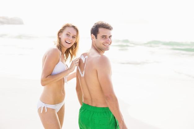 Женщина делает символ сердца на спине мужчины во время нанесения солнцезащитного крема Premium Фотографии