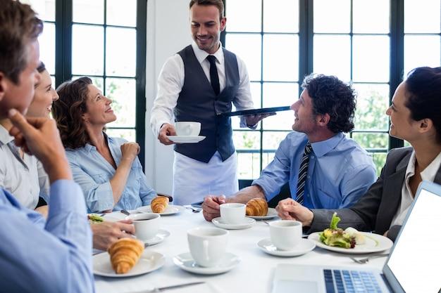 ビジネスの人々にコーヒーを提供するウェイター Premium写真