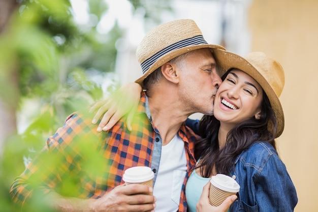 コーヒーを飲みながら陽気な女性にキスをする男性 Premium写真