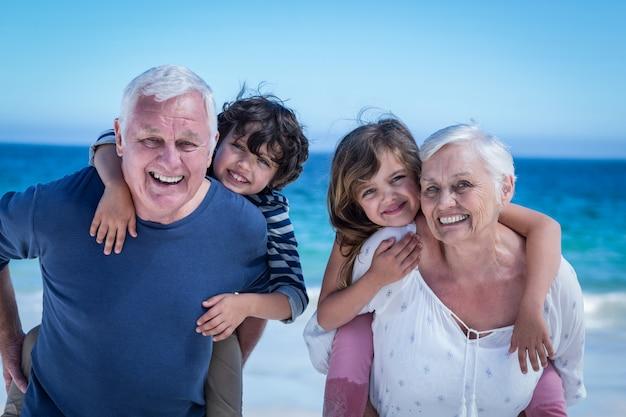 子供たちにおんぶを与える幸せな祖父母 Premium写真
