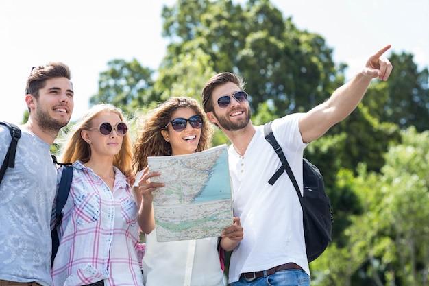 マップを押しながら屋外を指しているヒップの友達 Premium写真