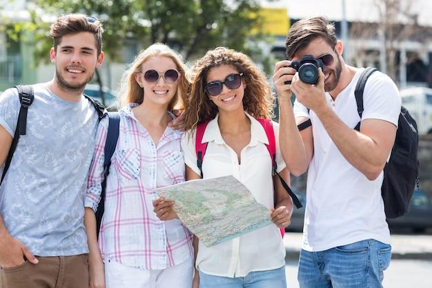 マップを押しながら市内のカメラで写真を撮るヒップの友達 Premium写真
