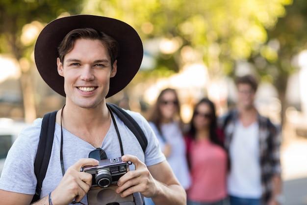 デジタルカメラを押しながらカメラに笑顔のヒップ男 Premium写真