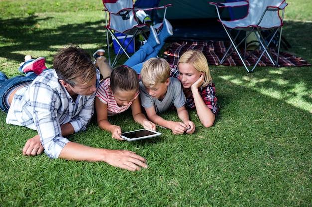 Семья лежа на траве и используя цифровую таблетку Premium Фотографии