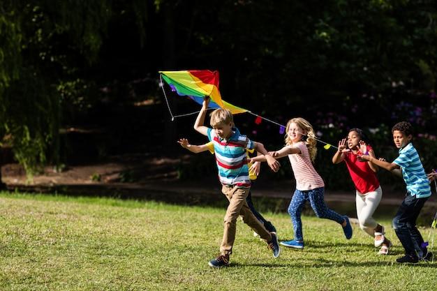 Счастливые дети играют с воздушным змеем Premium Фотографии
