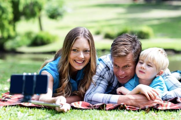 Родители и сын, принимая селфи на мобильный телефон Premium Фотографии