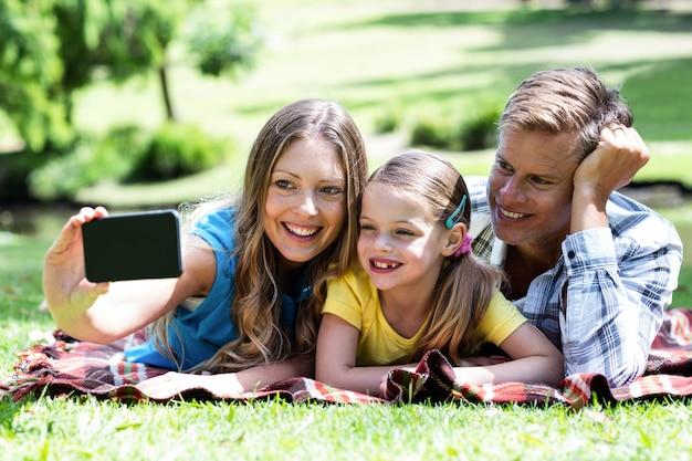 Родители и дочь, принимая селфи на мобильный телефон Premium Фотографии
