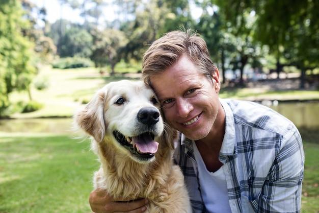 公園で彼のペットの犬と笑みを浮かべて男 Premium写真