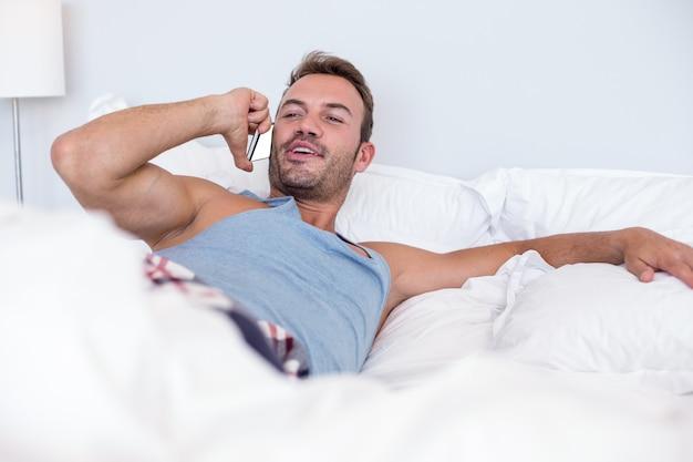 Молодой человек лежал на кровати Premium Фотографии