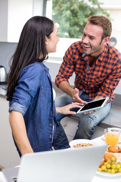 ラップトップとデジタルタブレットを使用して対話するカップル Premium写真