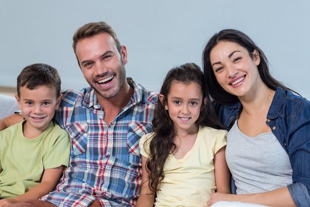 Семья сидит на диване и улыбается Premium Фотографии