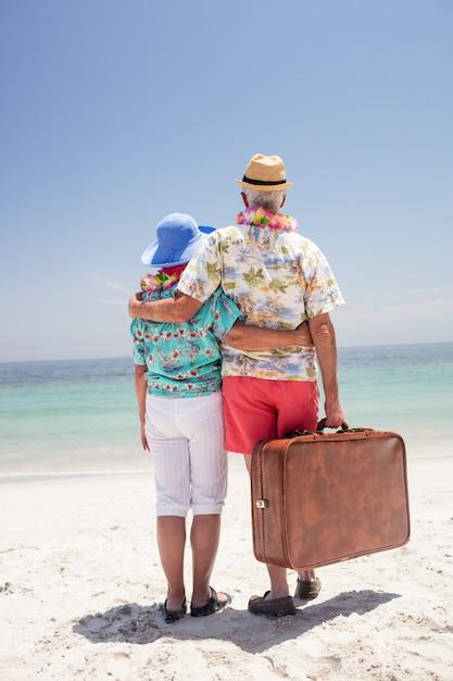 Вид сзади старшие пары носить гирлянду и глядя на море Premium Фотографии