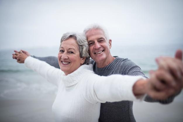 広げられた腕によって立っている幸せな先輩カップルの肖像画 Premium写真