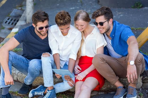 タブレットを見て、市内の歩道に座っている腰の友人 Premium写真