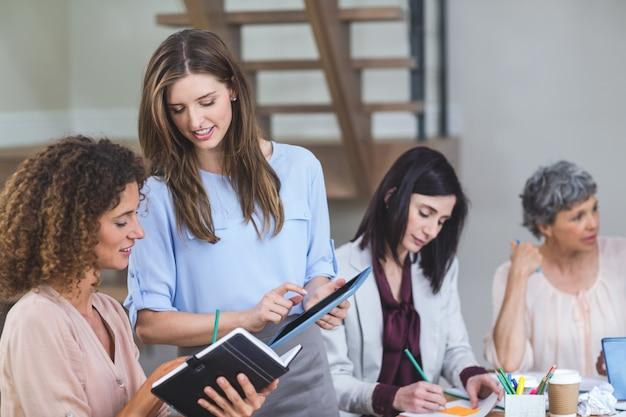デジタルタブレットで議論する女性ビジネス部門の同僚 Premium写真