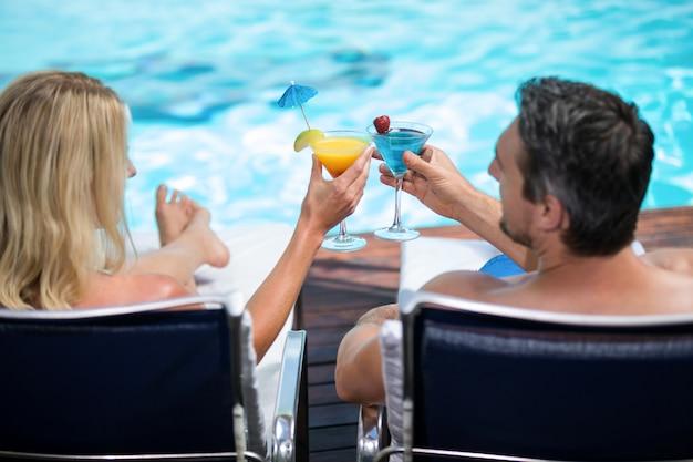 サンラウンジャーでリラックスしながらマティーニグラスを乾杯カップルの背面図 Premium写真