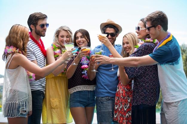 カクテルのグラスを乾杯する友人のグループ Premium写真