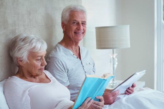 Счастливый старший мужчина с женой, чтение книги в спальне Premium Фотографии
