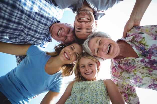 空に対してハドルを形成する陽気な家族 Premium写真