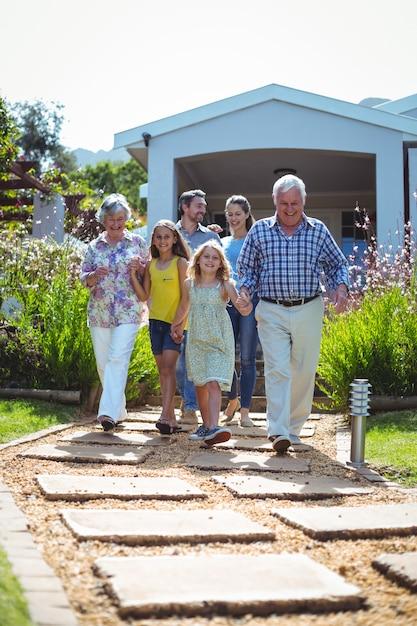 歩道を歩いて笑う多世代家族 Premium写真