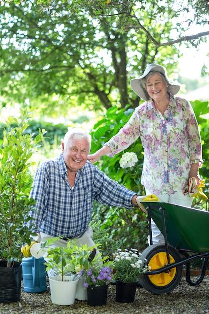 鉢植えの植物と夫によって立っている年配の女性 Premium写真