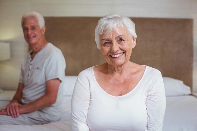 ベッドに座っている夫と年配の女性 Premium写真