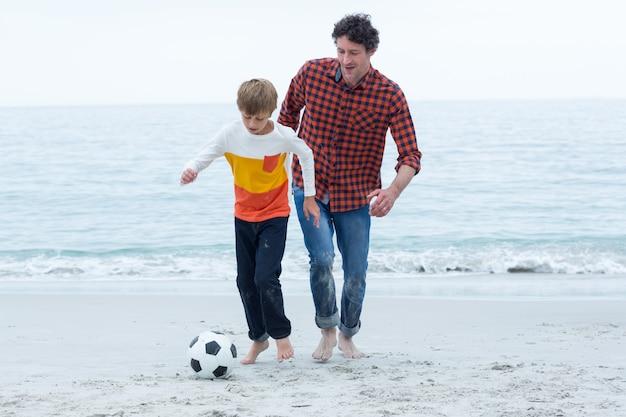 父と息子のビーチでサッカーをして Premium写真