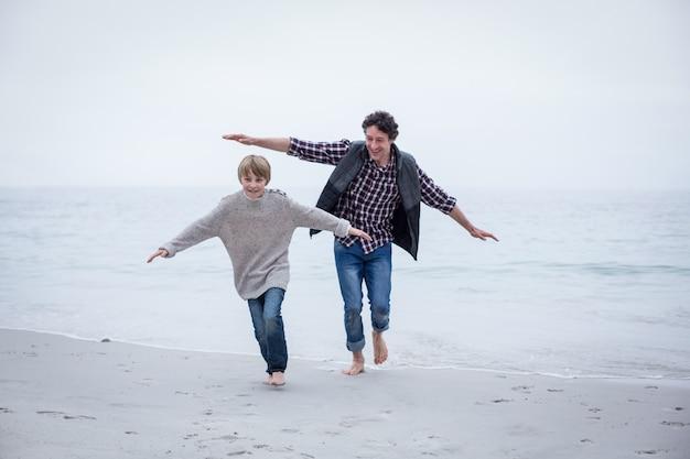 父と息子の両腕でビーチを走る Premium写真