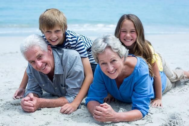 海岸で祖父母に横たわっている子供 Premium写真