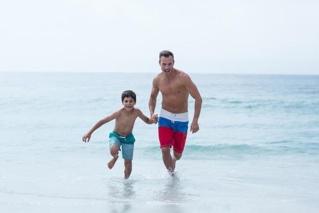 ビーチで走っている父と息子の全長 Premium写真