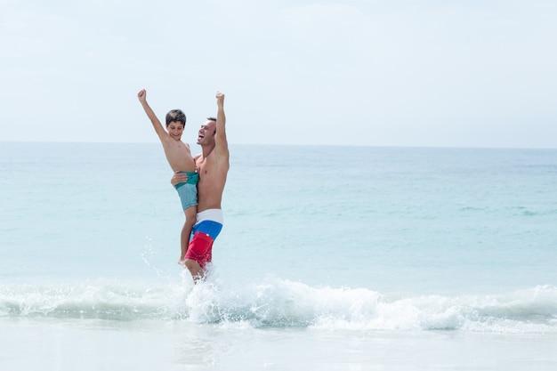 父と息子の腕を上げるビーチで楽しんで発生 Premium写真