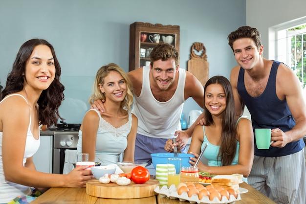 幸せな男性と女性の友人が家の台所で料理 Premium写真