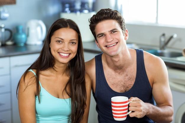 自宅でコーヒーカップを保持している男と幸せな女 Premium写真