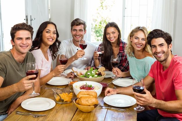ランチをしながらワイングラスを保持している幸せな友人の肖像画 Premium写真