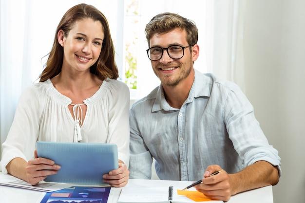 オフィスでデジタルタブレットを使用して男性と女性の同僚の肖像画 Premium写真