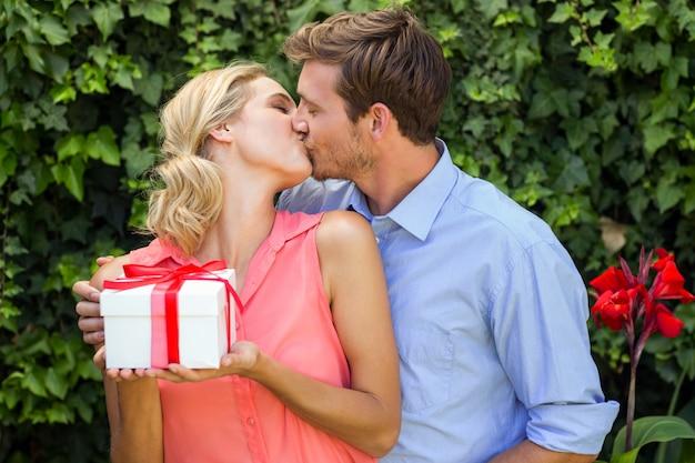 フロントヤードで女性に贈り物をしながらキスをする男性 Premium写真