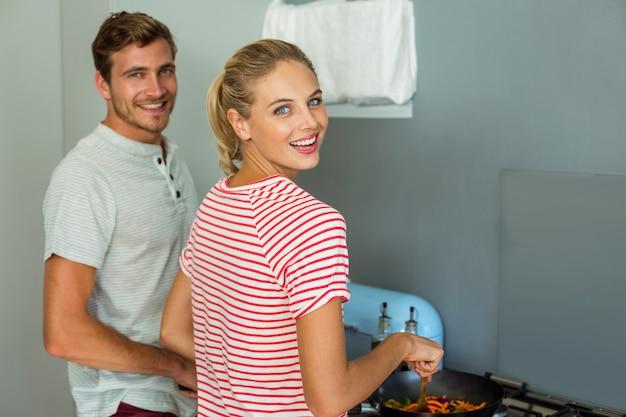 自宅で料理の若いカップルの肖像画 Premium写真