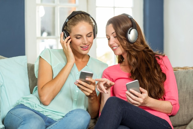 携帯電話を保持している幸せな女性の友人 Premium写真
