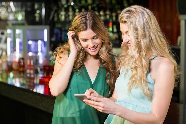 Улыбающиеся друзья с помощью смартфона Premium Фотографии