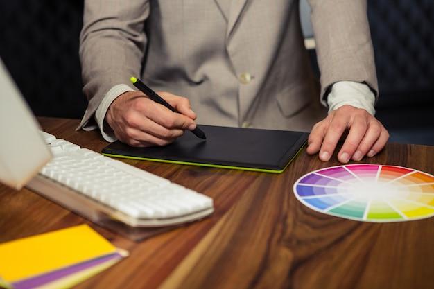 Творческий бизнесмен с помощью графического планшета Premium Фотографии