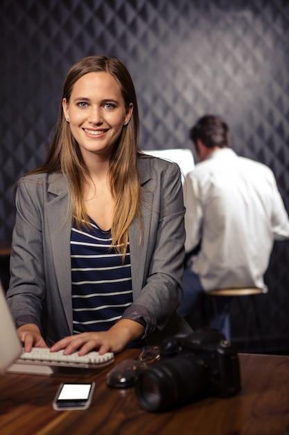 Творческая коммерсантка используя компьютер Premium Фотографии