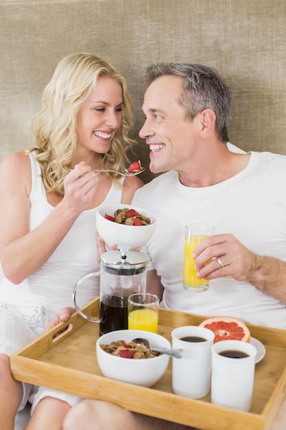 かわいいカップルが彼らの部屋でベッドで朝食をとります。 Premium写真