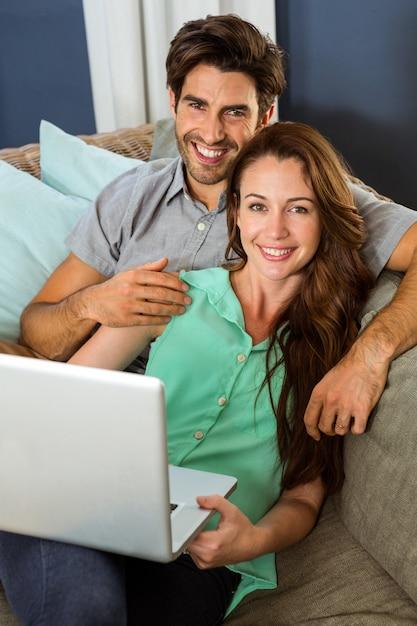ソファに座ってラップトップを使用して若いカップルの肖像画 Premium写真