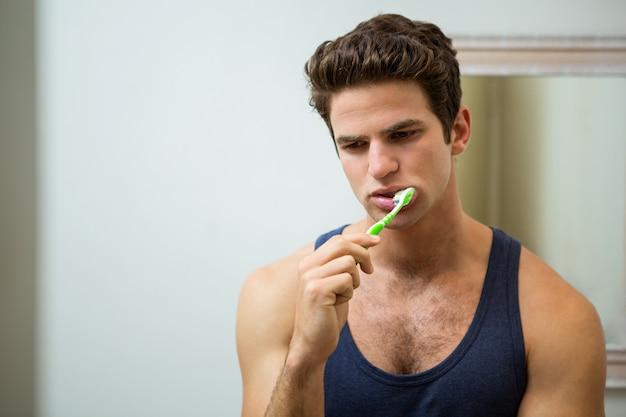 若い男が浴室で彼の歯を磨く Premium写真