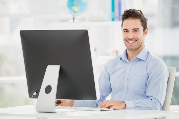 コンピューターで作業して笑顔の実業家 Premium写真