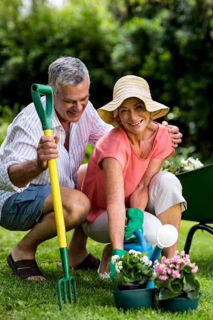 庭で園芸用品と笑顔の年配のカップル Premium写真