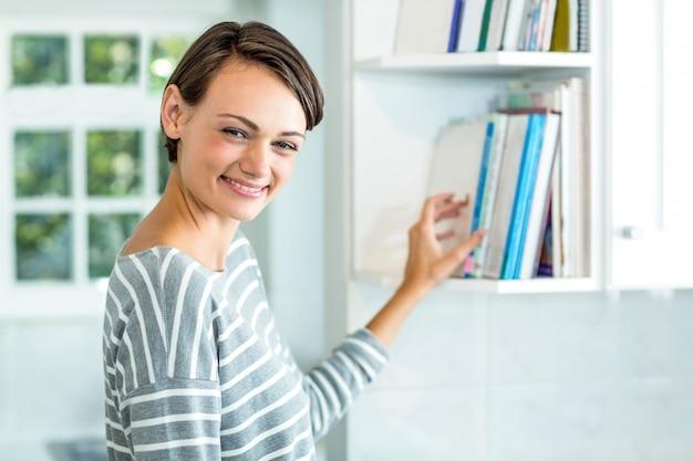 自宅のキャビネットから美しい女性ピッキング本 Premium写真