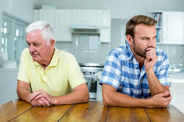 緊張した父と息子が台所のテーブルに座って Premium写真
