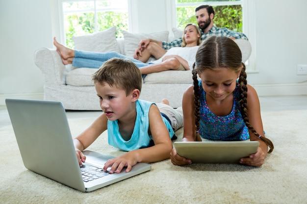 ソファでくつろいでいる両親に対してテクノロジーを使用している兄弟 Premium写真