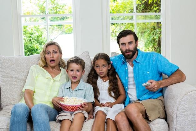 テレビを見ながら笑っている驚いた家族の肖像 Premium写真